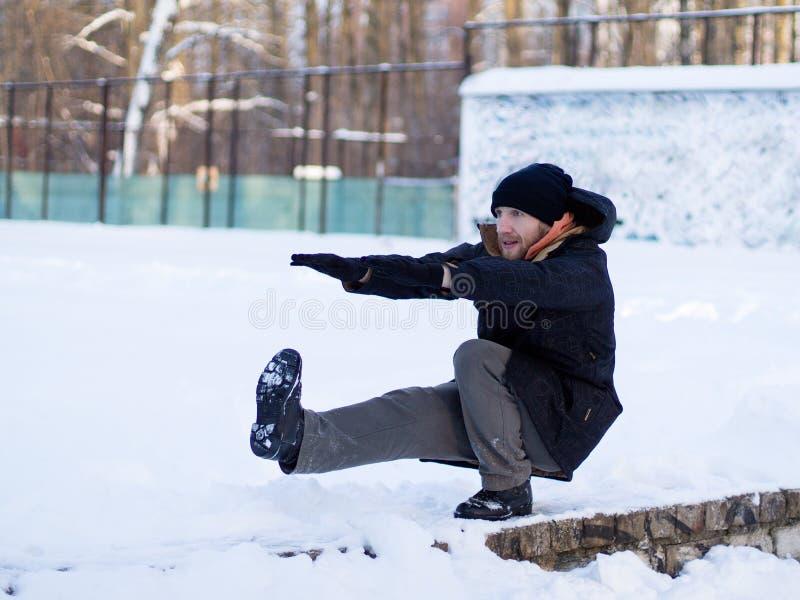 Молодой человек в одежде зимы спорт делая сидения на ...