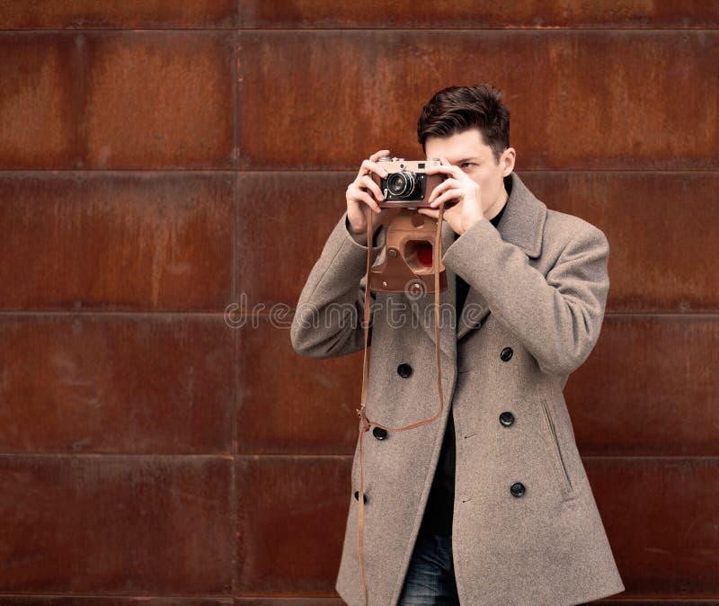 Молодой человек в пальто фотографирует модельный винтажную камеру на стене металла ржавой стоковое изображение rf