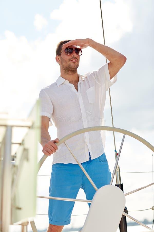 Молодой человек в рулевом колесе солнечных очков на яхте стоковое фото rf