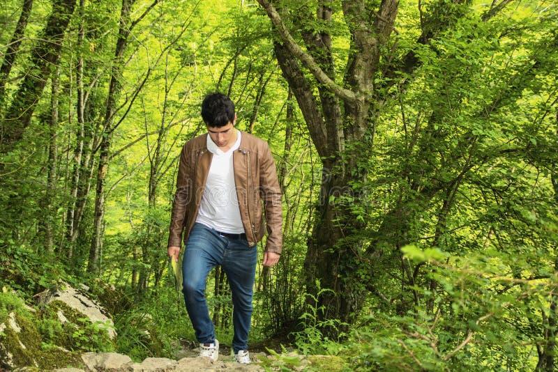 Молодой человек в сочном зеленом пейзаже горы стоковая фотография