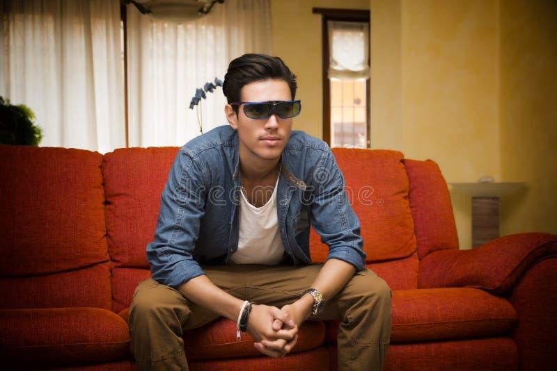 Молодой человек в стеклах 3d сидя смотрящ телевидение стоковая фотография rf