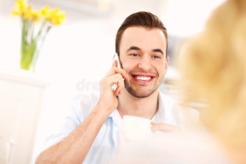 Молодой человек говоря на телефоне в кухне стоковые изображения rf
