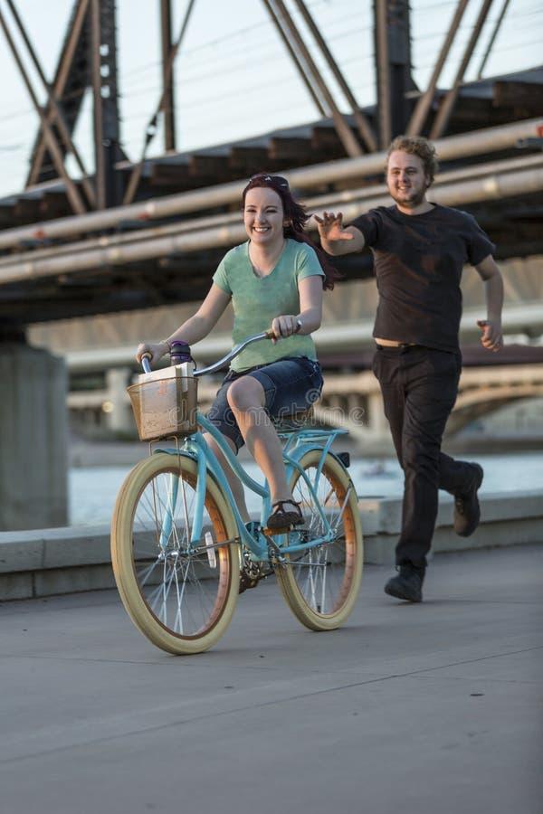 Молодой человек гонит девушку на велосипеде стоковая фотография