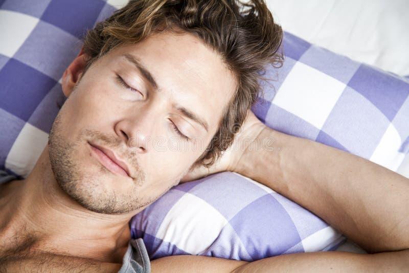 Молодой человек лежа в кровати стоковое изображение rf