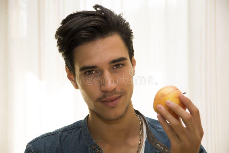 Молодой человек держа большое очень вкусное зрелое яблоко стоковое фото