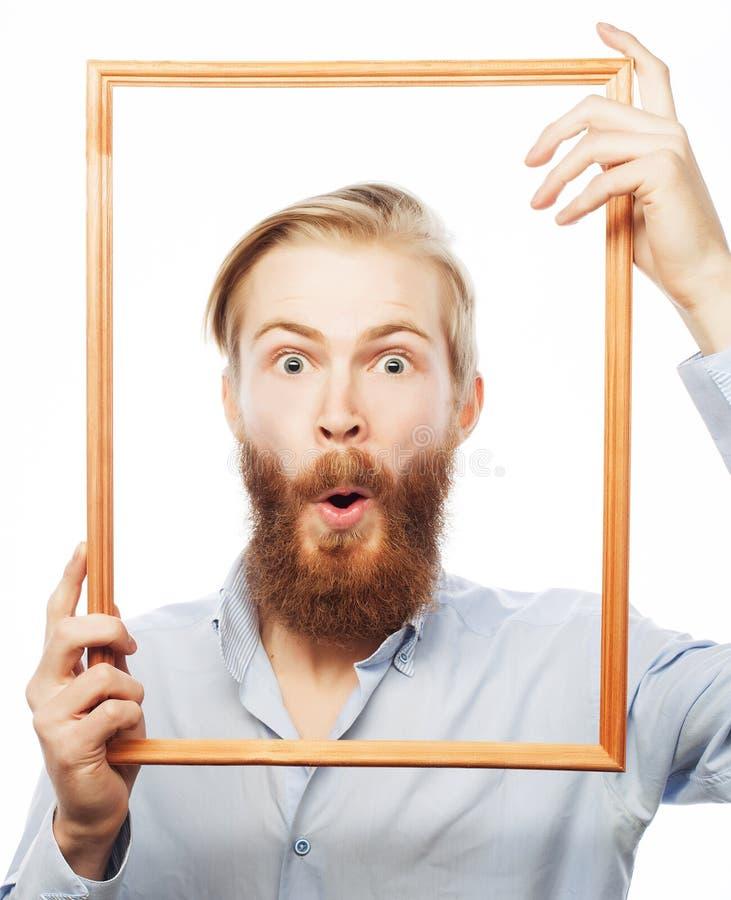 Молодой человек держа картинную рамку стоковая фотография