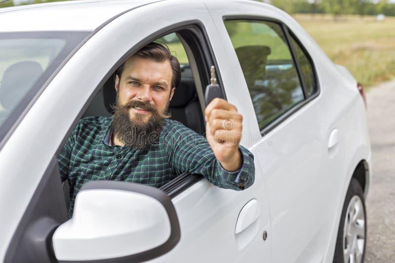 Молодой человек держа ключ его нового автомобиля стоковое фото rf