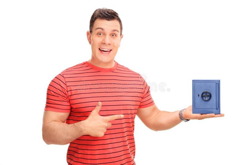 Молодой человек держа малый голубой сейф стоковая фотография rf