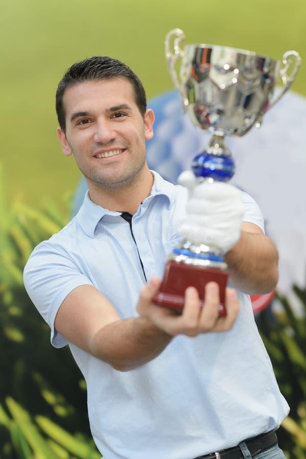 Молодой человек держа трофей стоковая фотография