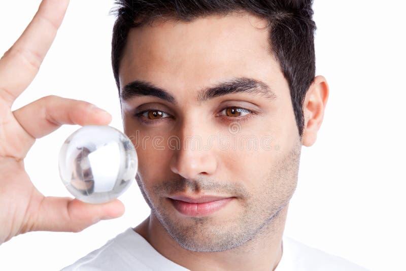 Молодой человек держа хрустальный шар стоковое изображение rf