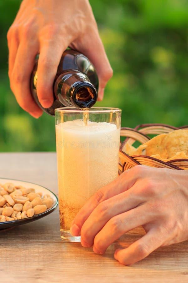Молодой человек держит бутылку пива и заполняет стекло стоковое фото