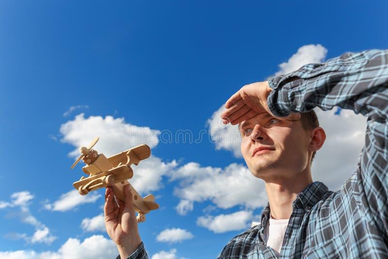 Молодой человек держит самолет игрушки деревянный в руке против голубого неба и смотрит в расстояние стоковые фотографии rf