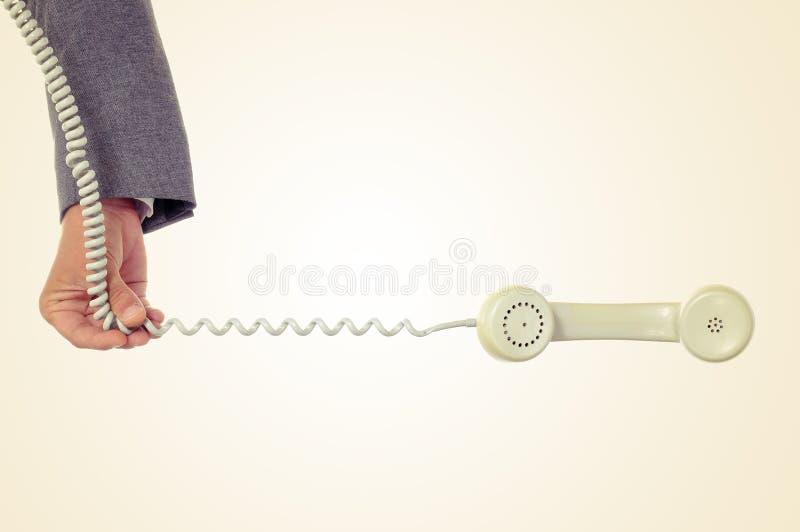 Молодой человек держит шнур телефона стоковое фото rf