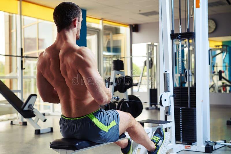 Молодой человек делая тренировку для задней части в спортзале стоковые изображения
