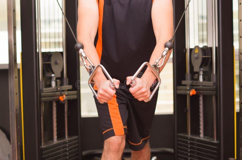 Молодой человек делая тренировку для трицепса в спортзале стоковые фото