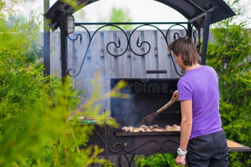Download Молодой человек жарит стейки на гриле внешнем в его дворе Стоковое Изображение - изображение насчитывающей природа, комфорт: 40587209