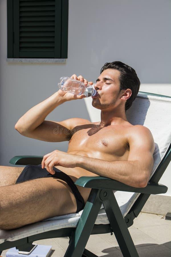 Молодой человек загорая и выпивая от бутылки с водой стоковые фото