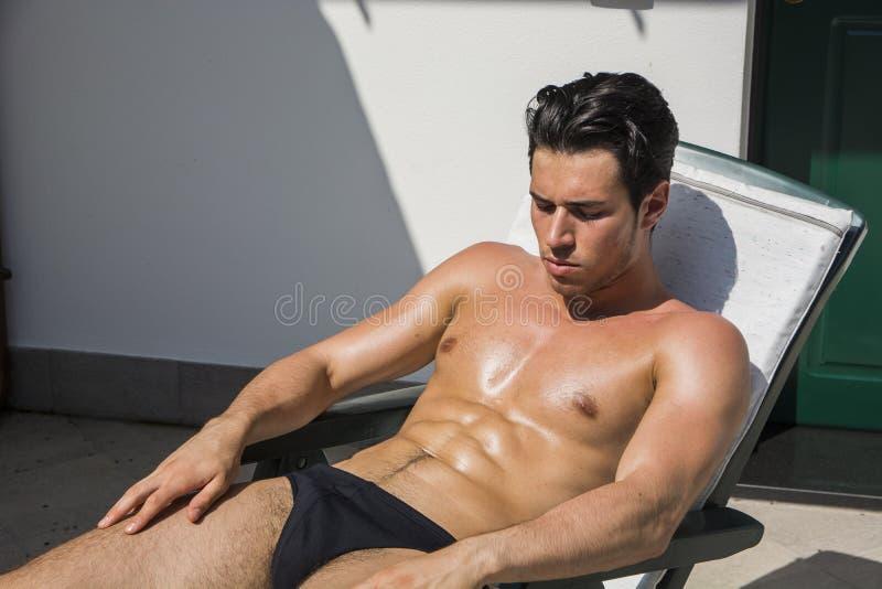 Молодой человек загорая на кресле для отдыха стоковые изображения rf