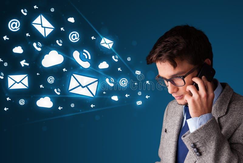 Молодой человек звоня телефонный звонок с значками сообщения стоковое изображение