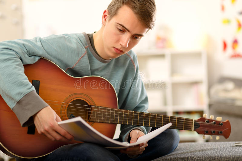 Молодой человек играя акустическую гитару стоковая фотография rf