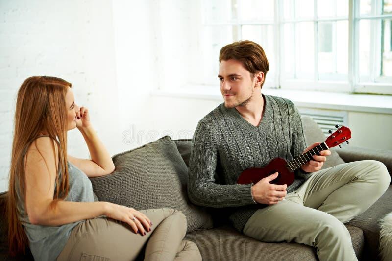 Молодой человек играя гавайскую гитару к его подруге стоковая фотография rf