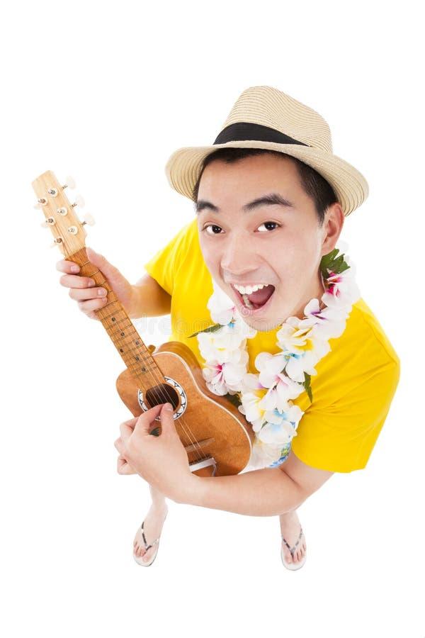 Молодой человек играя гавайскую гитару стоковые изображения rf