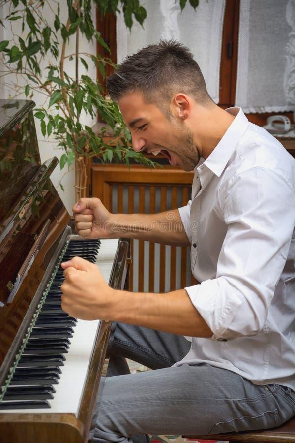 Молодой человек играя классический рояль, крича стоковое фото
