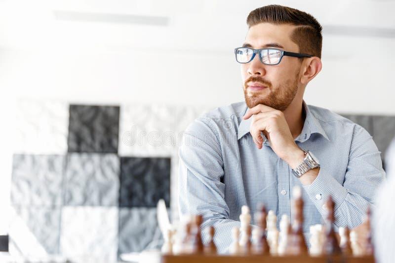 Молодой человек играя шахмат стоковое фото