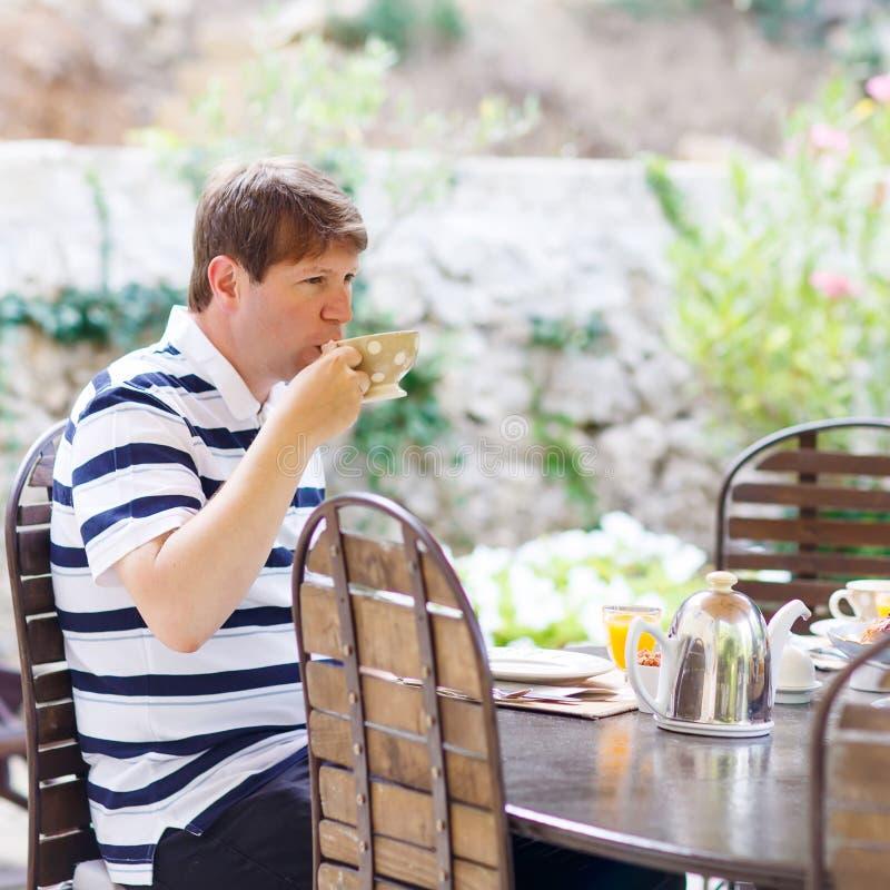 Молодой человек имея завтрак снаружи в лете с различными вареньями, стоковая фотография rf