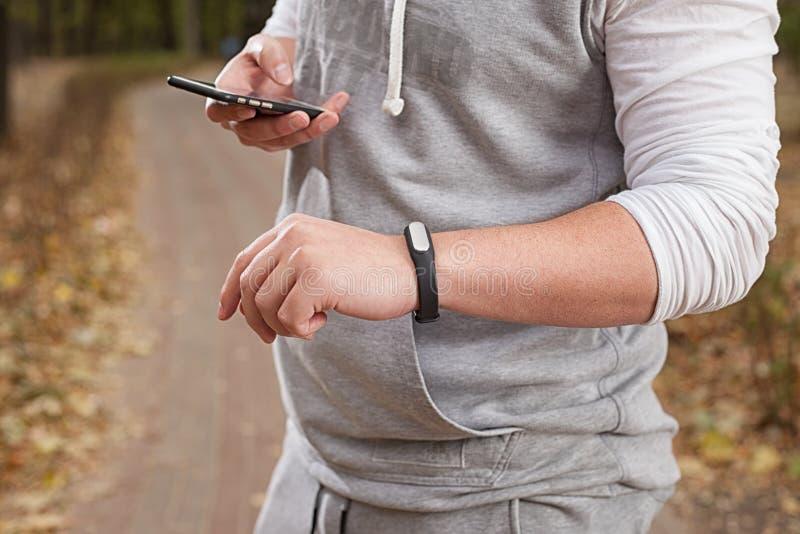 Молодой человек используя браслет фитнеса во время стоковые изображения rf
