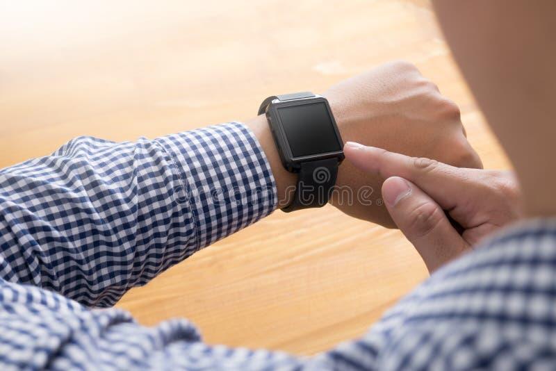 Молодой человек используя вахту сенсорного экрана умный стоковые фото