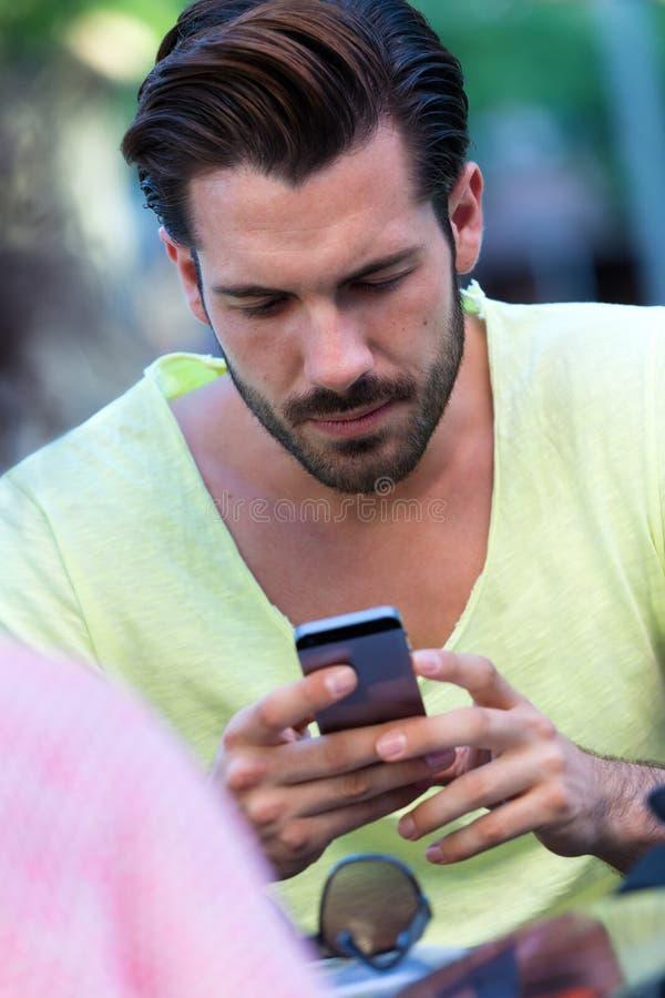 Молодой человек используя его мобильный телефон в улице стоковая фотография