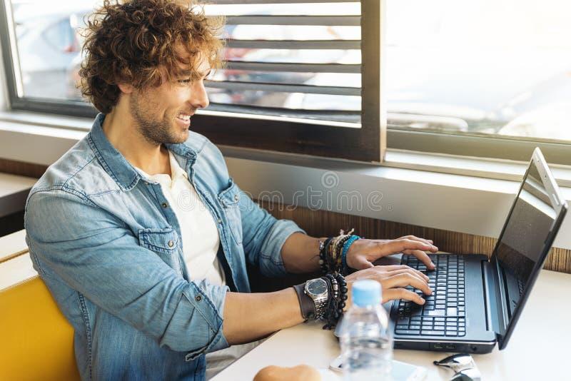 Молодой человек используя компьтер-книжку пока для того чтобы иметь обед стоковое фото