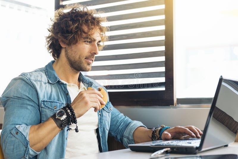 Молодой человек используя компьтер-книжку пока для того чтобы иметь обед стоковое фото rf