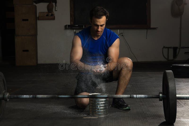 Молодой человек используя мел спортзала стоковое изображение rf