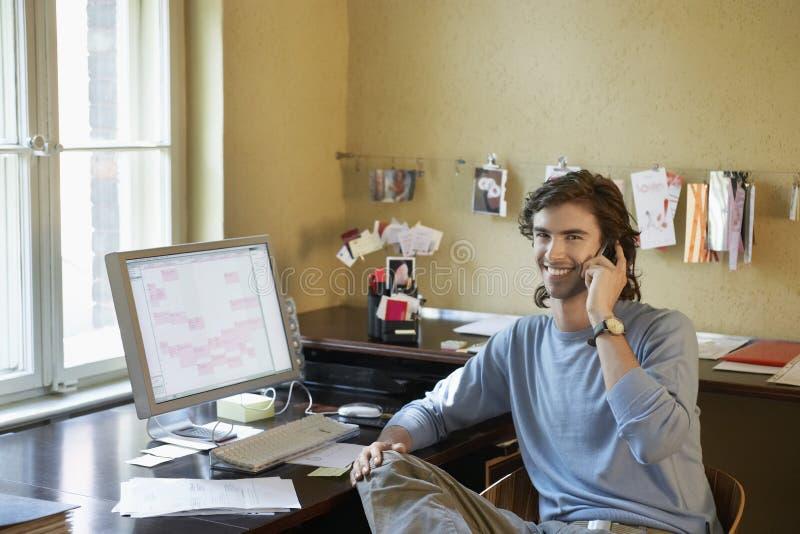 Молодой человек используя мобильный телефон в офисе стоковые изображения rf