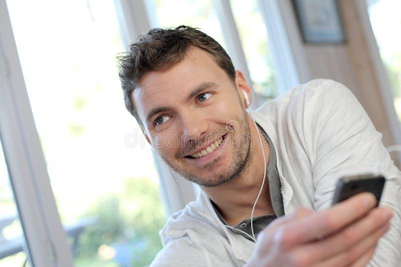 Молодой человек используя мобильный телефон и наушники стоковая фотография rf