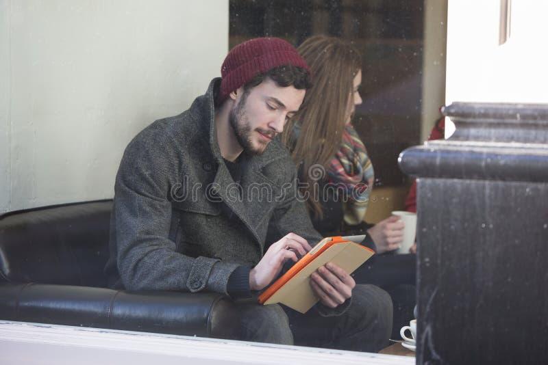Молодой человек используя таблетку стоковые изображения rf