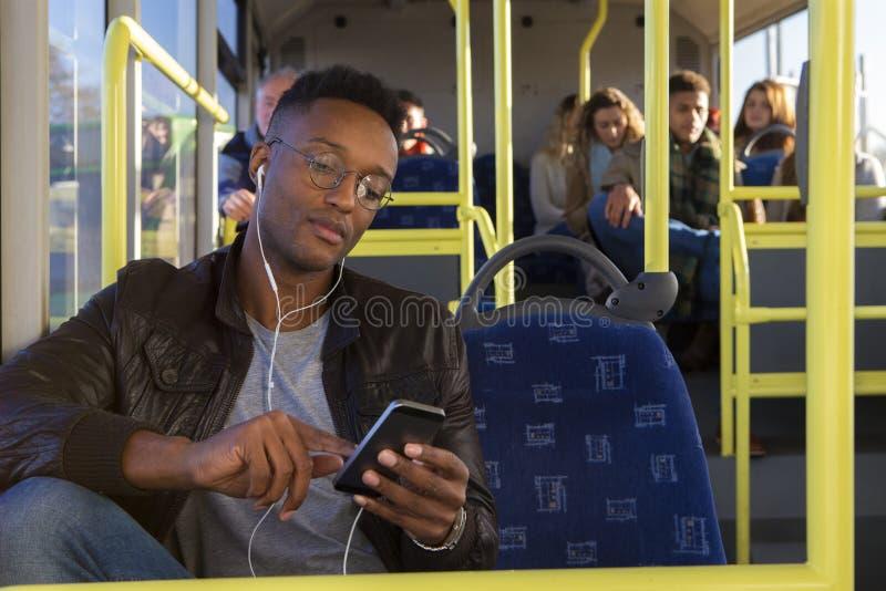 Молодой человек используя smartphone на шине стоковое фото rf