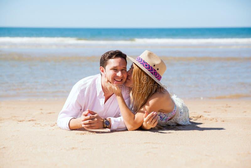 Молодой человек и его жена ослабляя на пляже стоковая фотография