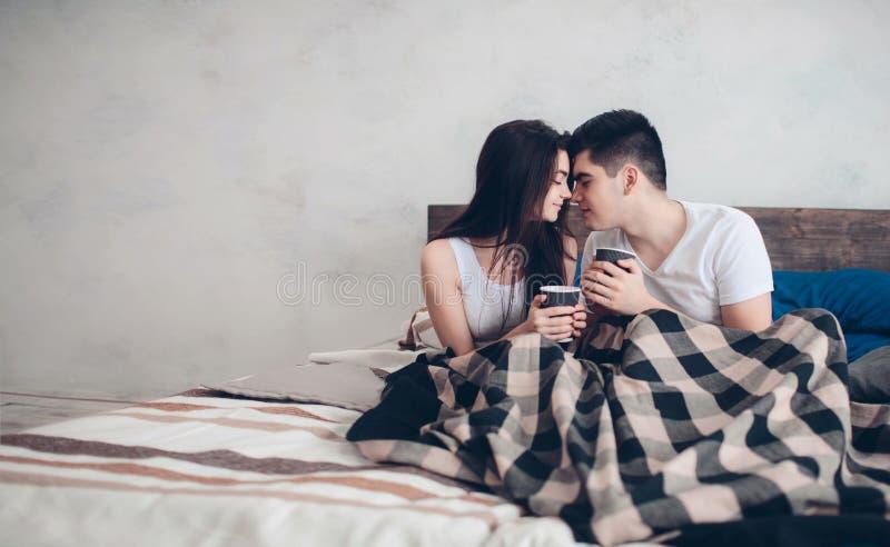Молодой человек и женщина выпивают кофе в утре в кровати Романтичное утро дома стоковые изображения