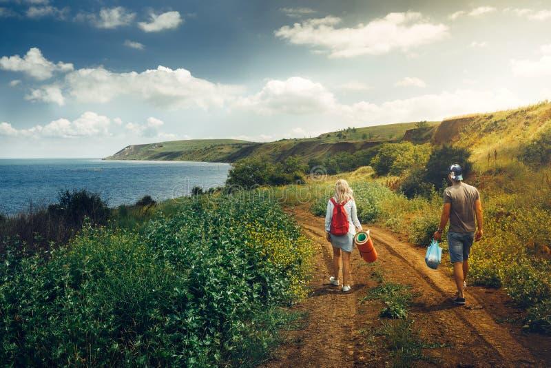 Молодой человек и женщина при рюкзак, взгляд от позади, идя вдоль дороги к перемещению приключения моря ослабляют концепцию стоковая фотография