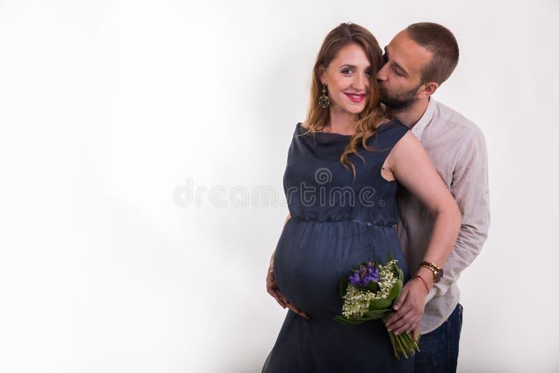 Молодой человек и красивая беременная женщина на светлой предпосылке стоковое фото rf