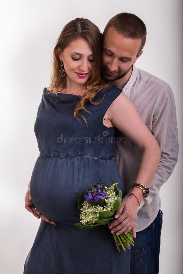 Молодой человек и красивая беременная женщина на светлой предпосылке стоковая фотография
