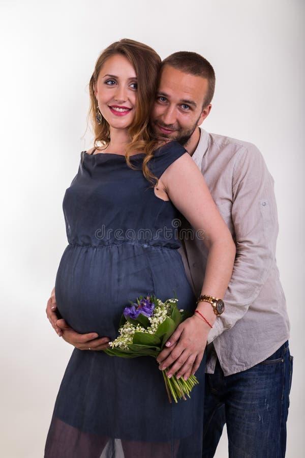 Молодой человек и красивая беременная женщина на светлой предпосылке стоковые фото