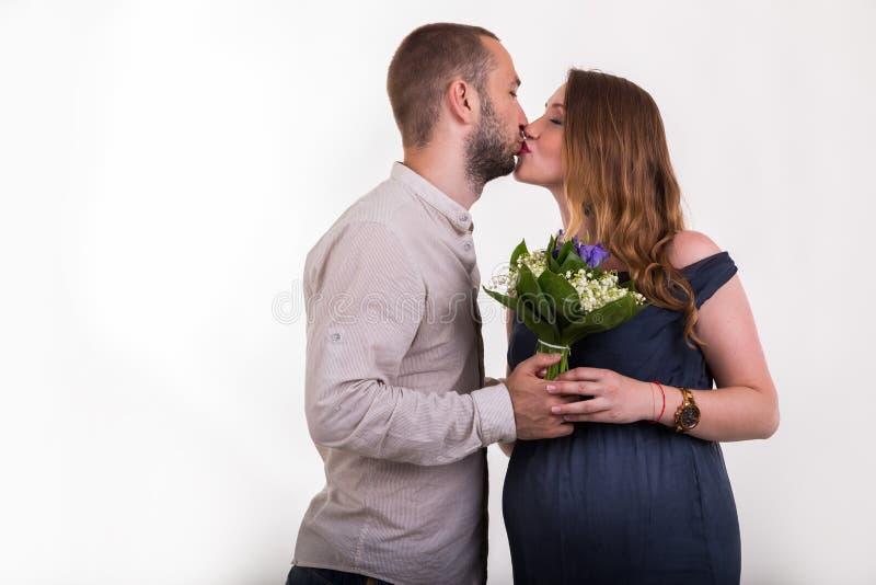 Молодой человек и красивая беременная женщина на светлой предпосылке стоковое изображение