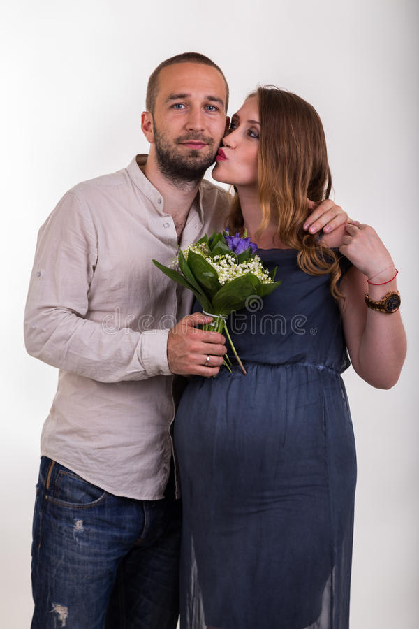 Молодой человек и красивая беременная женщина на светлой предпосылке стоковые изображения