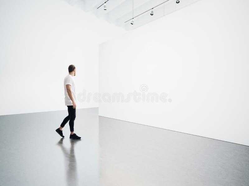 Молодой человек идя в пустую, белую галерею стоковое фото rf