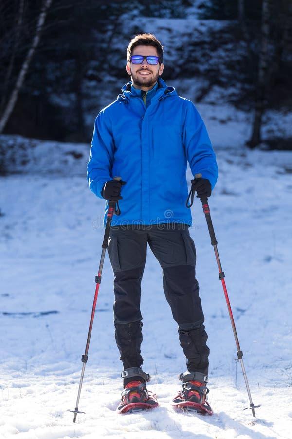 Молодой человек идя в snowshoes над предпосылкой зимы стоковые изображения