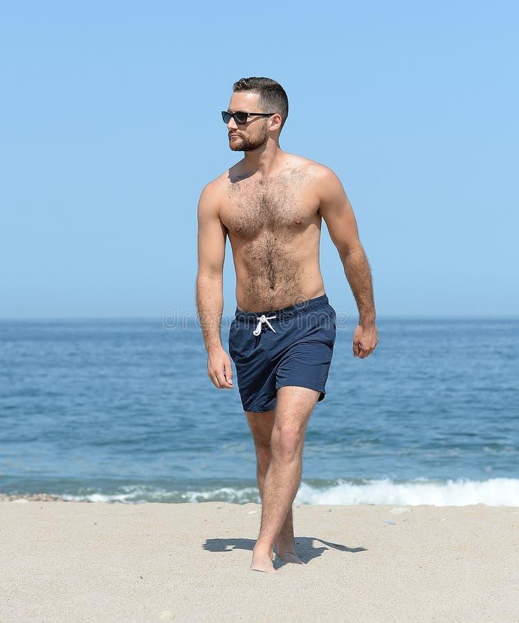 Молодой человек идя на песчаный пляж стоковые фотографии rf